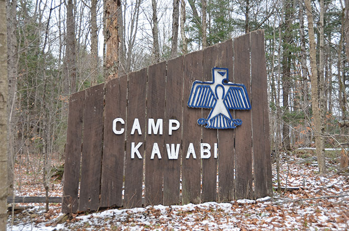 Sign for Camp Kawabi with thunderbird icon