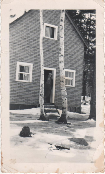 Men in the doorway of a brick building with birch trees