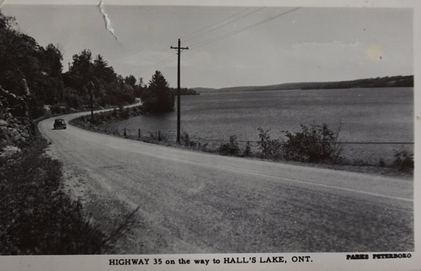 Car driving along road next to lake in the past