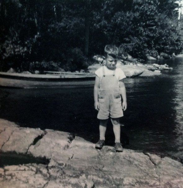 little boy standing on a shore