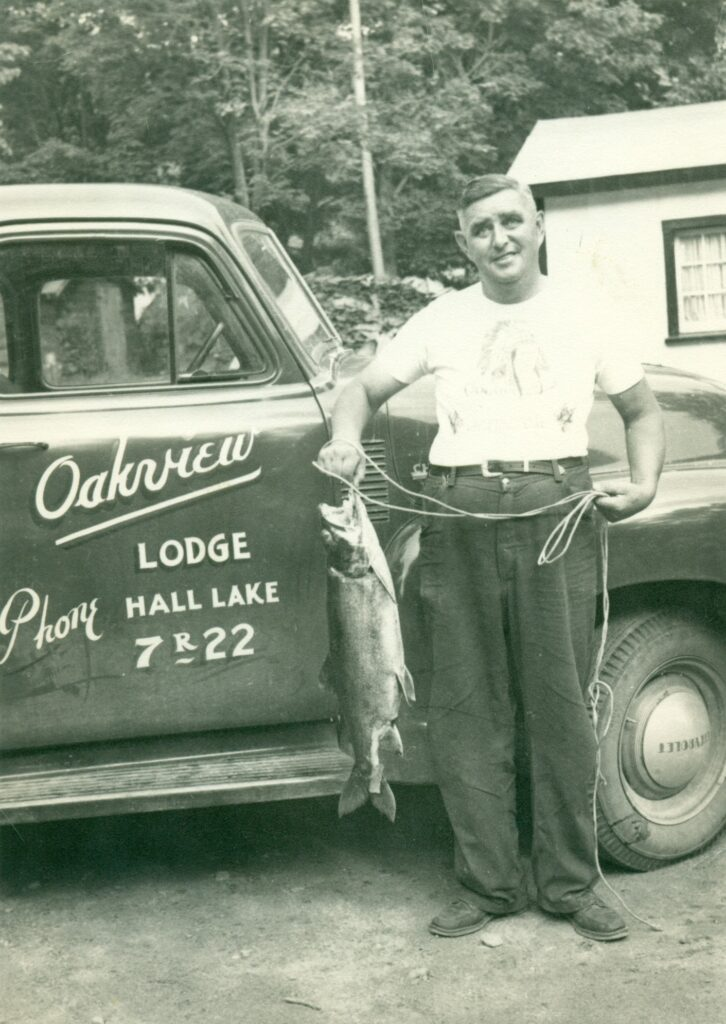 man with fish next to truck