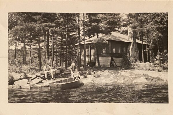 People in a boat in front of a cottage