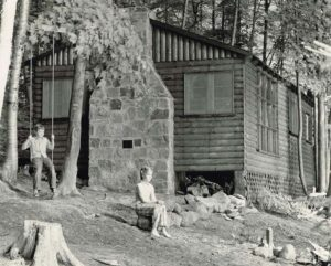 kids in front of a log cabin